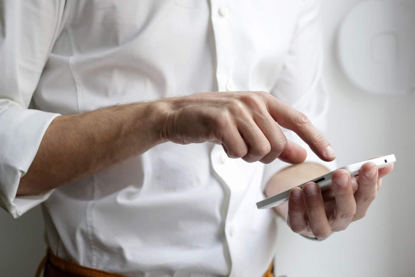 Man wearing a white shirt using his phone